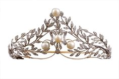 A belle epoque diamond and pearl tiara, designed as a series of laurel fronds in a wreath formation. Centering on a diamond bow, with a pearl centre and pearls each side, and topped with a larger pearl.