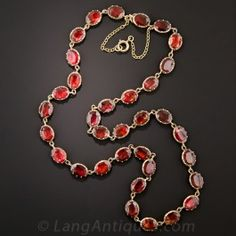 Dating back to early-to-mid-nineteenth century Great Britain, a gorgeous, classic, Georgian, or early-Victorian, rivière necklace aglow with 34 foil-backed garnets, collet-set in 9ct. rosy-yellow gold. When off-duty, it resides in its original fitted box from Barraclough & Sons, Leeds. 16 inches long.