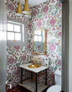 The pomegranate-patterned wallpaper in a downstairs powder room is by Idarica Gazzoni. The gold-bowled sink was there when the couple moved in; they just polished it.