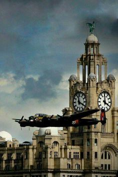 A Lancaster bomber flying over the River Mersey, and past the Royal Liver Building, Liverpool