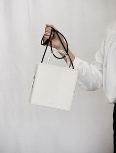 """A structural box bag from Building Block. Smooth ivory leather, clear lucite handle, black rubber shoulder strap, zip closure. Size7"""" x 7"""" x 2.75"""" ColorIvory"""