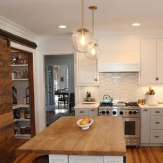 white kitchen + pendants + woodtop island + sliding barndoor