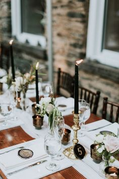 Gold candlesticks with black taper candles + agate slice name cards | Image by M2 Photography
