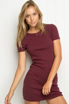Jenelle Dress- this burgundy shirt dress has a  natural shape and fit . The dress isn't very structured and is made from a soft T-shirt materiel, This material allows the dress to follow the natural body outline of the model . this shape is extremely flattering , emphasizing the naturel waistline and curves of the model.
