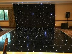 The black back drop and sparkly black dance floor is available to hire