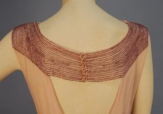 whitakerauction >Spring 2012>Clothing>LOT 716  BEADED CHIFFON EVENING GOWN with CAPE, 1930's. Sleeveless sweep trained pink gown having bands of plum iridill beads at waist, shoulder, and band above the triangular open back, (no under dress). Plum chiffon floor length cape.