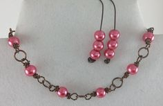 Earrings: Wire is knotted on one end, formed into shape on a ring sizer & pearls added.  Bracelet: Pearl links are created by twisting two strands 26g together and jumps formed with 20g wire.