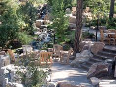 A stone pathway lined with boulders creates a natural walkway down to a seating area adorned with several rocking chairs — a peaceful setting to enjoy the nearby river.