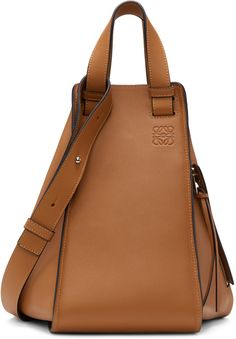 'Classic' calfskin tote in tan. Twin carry handles. Detachable and adjustable shoulder strap with post-stud fastening. Logo embossed at face. Zippered pocket at side. Zippered expansion panel at sides. Lanyard tab at throat. Patch pockets at interior. Detachable zip pouch on leather lanyard at interior. Textile lining in black. Bumper studs at base. Silver-tone hardware. Tonal stitching. Approx. 6.5