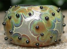 """This bead has a base of light brown transparent - with the transparent base you get more of a """"halo"""" and more color variations. I make my rubino stringer as thin as I can (and still be able to handle it!) I melt it in fairly slowly at first then heat it more to get the spread... The more you heat, the more it spreads - so if you use a thicker stringer, you're not going to get as much contrast between the background and the edges of the rubino's """"halo""""."""