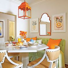 "Colorful Breakfast Nook | A custom octagonal, quartz-topped table surrounded by three chairs and a freestanding banquette ""offers a lot of seating in a tight space,"" says designer Melissa Haynes. The pair of fruit drawings gives a subtle nod to the room's color scheme."