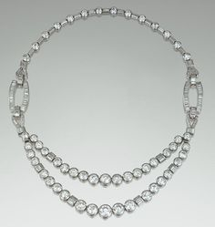 DIAMOND NECKLACE,  1930S   Decorated to the front with a swag of graduated collet-set circular-cut diamonds, interspersed with baguette stones, suspended from open work elements set with similar stones, the back row designed as a line of circular-cut diamonds alternating with baguette stones, mounted in white gold and platinum,  French assay marks.