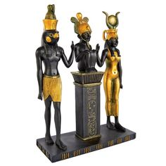 """The gods, Isis with her horned disk, Osiris with his feathered crown and their son Hours with his falcon head, present themselves in proud array in this ancient replica design Toscano statue. The etched hieroglyph includes the heraldic phrase, """"I grant you encompassing bravery and total victory."""" Cast in quality designer resin, this Egyptian replica is finished in faux ebony and gold for proud display in home or gallery."""