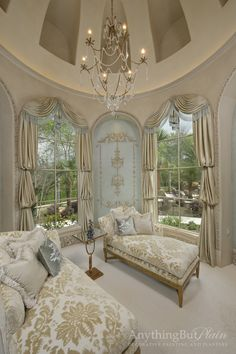 Regal sitting room in muted colors. Bishop sleeve draperies with swags on large arched windows.