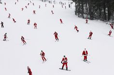 Skiers and snowboarders dressed as Santa Claus head down the slope at Sunday River, Maine.