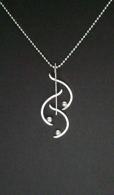 The pendant is handmade of 1/2 round sterling wire that I forged flat and textured, square sterling wire and melted sterling balls. It measures 3/4 x 2 inches. It hangs on an 18 inch sterling silver bead chain.    SS555