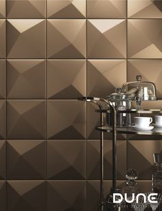 ORIGAMI BRONZO - 25X25cm -   Tile with symmetrical 3D relief, with diagonal division. In a metallic bronze colour, allowing for plenty of variation in the way it is used to achieve a play of volumes that accentuate the light. #duneceramica #creativity #tiles #decoration #design #home #interiors #lifestyle #architecture #style #fashion #creatividad  #azulejos #diseño #decoración #casa #interiores #estilodevida #arquitectura #estilo … www.dune.es