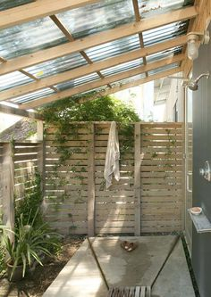 polycarbonate roof, shower, slat privacy fencing with plantings, trough drain, built in figures, door to interior