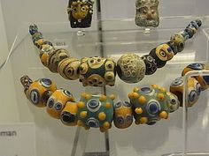 Rod formed pendant and beads from the Eastern Mediterranean. V&A