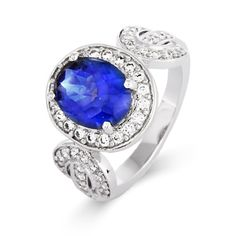 The ring features an oval blue tanzanite CZ center stone with a halo of white CZs and side designs. This would be a beautiful gift for a loved one.