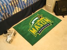 """George Mason Starter Rug 20""""x30"""" by Fanmats. $13.68. George Mason Starter Rug 20""""x30""""Decorate your home or office with area rugs by FANMATS. Made in U.S.A. 100% nylon carpet and non-skid recycled vinyl backing. Officially licensed and chromojet printed in true team colors. Please note: These products are custom made. The normal lead time is about 7-10 business days. However, the putting mats and carpet tiles do take a little longer, about 14-21 business days.***This it..."""