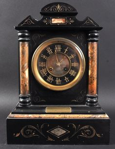 A 19TH CENTURY BLACK SLATE ARCHITECTURAL MANTLE CLOCK.
