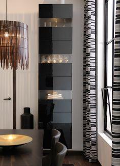 Ein Raum mit BESTÅ Aufbewahrungskombination schwarzbraun/Hochglanz Schwarz an der Wand, daneben BETEENDE Dekovase in Schwarz, LAPPLJUNG RAND Gardinenpaar weiß/schwarz am Fenster und an der Zimmerdecke ROTVIK Hängeleuchte Bambus/braun