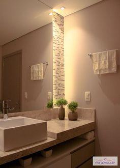 Iluminação na lateral do espelho valoriza o revestimento de pedra natural! Projeto by Basi Arquitetura.