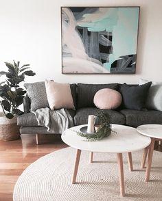 Living room | Dark grey lounge, pink cushions, artwork, wood