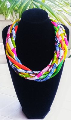 Colourful African print necklace woven and twisted to create an elegant design for any occasion. This is a colourful and fun necklace which will work well for any occasion. Let your spring season be fun with this necklace in your closet.  - The necklace measures approximately 20 inches and has a 2 inch extender chain for length adjustment. For different length variations, please chose your desired length before you checkout. - It is nicely packaged either in a box or wrapped thus makes it a…