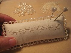 Beautifully embroidered pincushion. She shows you how to make the beaded edge.