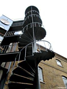 Einem Aussichtsturm gleich schraubt sich die Spindeltreppe an der Fassade eines ehemaligen Londoner Hafenspeichers in die Höhe. Und zu beachten - mit Dach. #smgtreppen