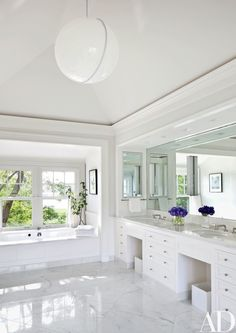 The adjoining marble-floored bath includes an acrylic pendant light from ABC Carpet & Home   archdigest.com