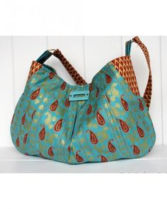 Using a paisley turquoise, brown, and gold fabric, Knitchick2 made this 100 percent cotton pleated purse with a turquoise medallion on the front.