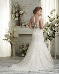 502 Bonny by Bonny Bridal - A beautiful trumpet silhouette with head to toe simplicity covered in Alencon lace and a tattooed lace back with button embellishments. Lace details include a scalloped hemline and lace that wraps around to create illusion cap sleeves. *Shown with belt style 9500 sold separately.