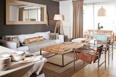 Living clásico y moderno en un departamento chico de San Fernando. Mesa ratona en madera y hierro, lámpara de pie y gran espejo para agrandar el espacio. Foto: Javier Csecs