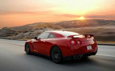 Red Nissan GTR rolling with a gorgeous sunset for a backdrop.