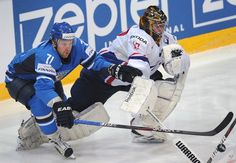 Finnish Leo Komarov (L) fights for the puck with French goalie Fabrice Lhenry during a preliminary round game of the IIHF International Ice Hockey World Championship in Helsinki on May 10, 2012