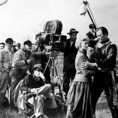 THE HORSE SOLDIERS (1958) - John Wayne & Constance Towers perform on location in Lousiana while director John Ford (seated) looks on - United Artists.