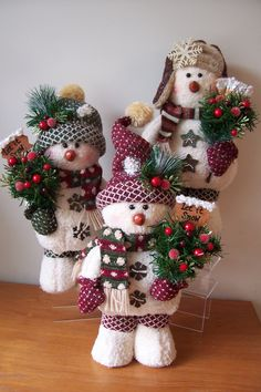 """Snowpuff Snowmen"" stand approximately 16"" tall and are embellished with rusty tin snowflake and star buttons, pine, berries, glittery leaves and a rustic frosted sign or snowbroom.  $18"