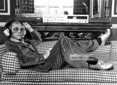 News Photo : British rock star Elton John listening to music...