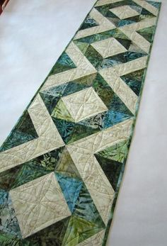 A blend of blue green batiks are gorgeous in this table runner. This runner will be a beautiful setting for your table. This runner would also be a wonderful gift to give someone. This table runner is