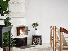 Kakelugn / decorative fireplace in the white and grey sitting room of a Swedish apartment. Anders Bergstedt. Entrance.