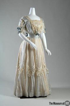 Silk Dress, c 1904.    This two-piece dress was designed to accentuate the youthful charm of Meta Beuhner, who was twenty years old when she wore it. The sheer fabric and pale color palette evoke a summer afternoon garden party. Delicate layers of coordinating ribbon and lace trim are applied in moderation, highlighting the vertical stripes and accentuating the lightness of the dress. A pleated gauze stripe emphasizes the small waist and softly bloused bodice of the s-curve silhouette.