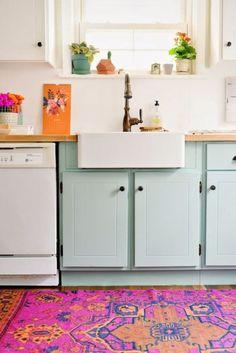 Cuisine féminine avec meubles vert d'eau et tapis  coloré. L'évier timbre d'office participe à l'esprit rétro de la cuisine.