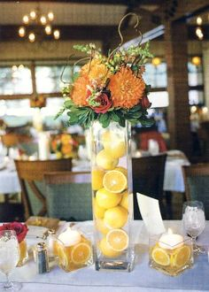 A taller vase with lemons and topped by the arrangement--smaller floating candles with more lemons to accent. Maybe for a sign-in table?