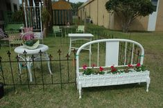 """This planter was just darling. As you can see it is made from an old iron headboard with a window box attached. They added some recycled turned legs to the front of the window box for support, and then a piece of trim across it just for """"pretty."""""""