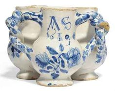 A LONDON DELFT DATED BLUE AND WHITE FUDDLING-CUP 1649, PROBABLY SOUTHWARK Formed from three baluster cups conjoined and pierced to form a single vessel, with entwined handles, one cup initialled and dated AS.1649 above a flower-spray, the other cups with further stylised flowers, the handles with trailing buds