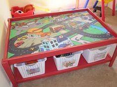 This is one of those rugs that you can buy for kids to play cars on.. What a great idea to make it into a table!