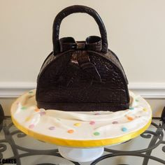 Haute Couture Handbag A marble chocolate and vanilla cake soaked in vanilla bourbon syrup filled with a middle layer of Nutella (a hazelnut creamy spread) and 2 layers of raspberry preserves. Frosted with a milk chocolate ganache filling, covered in a dark brown Satin Ice fondant in a alligator skin pattern.